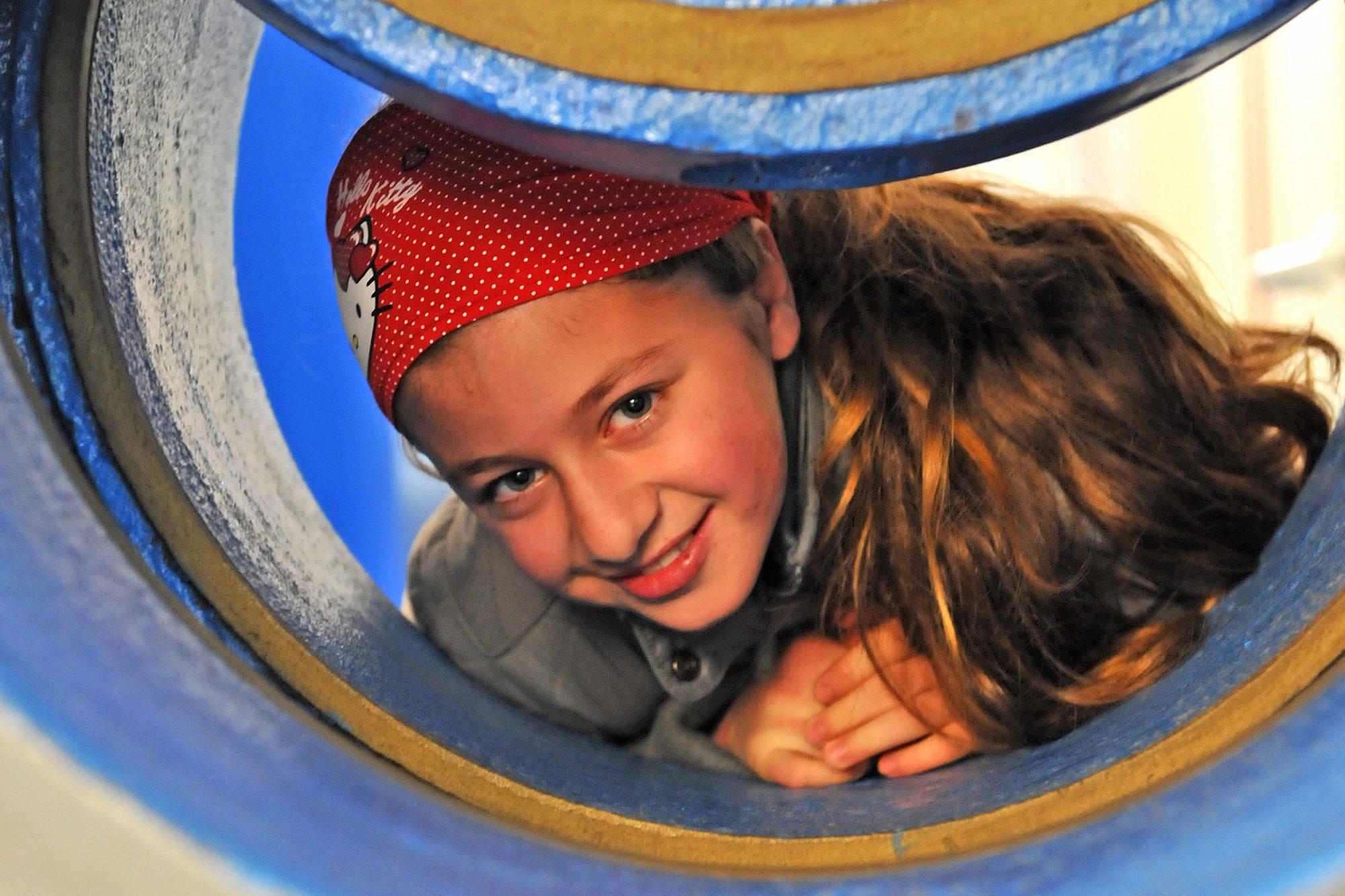 Ein Mädchen liegt in einer großen leeren Wasserleitung auf dem Bauch und schaut lächelnd aus dem Rohr.