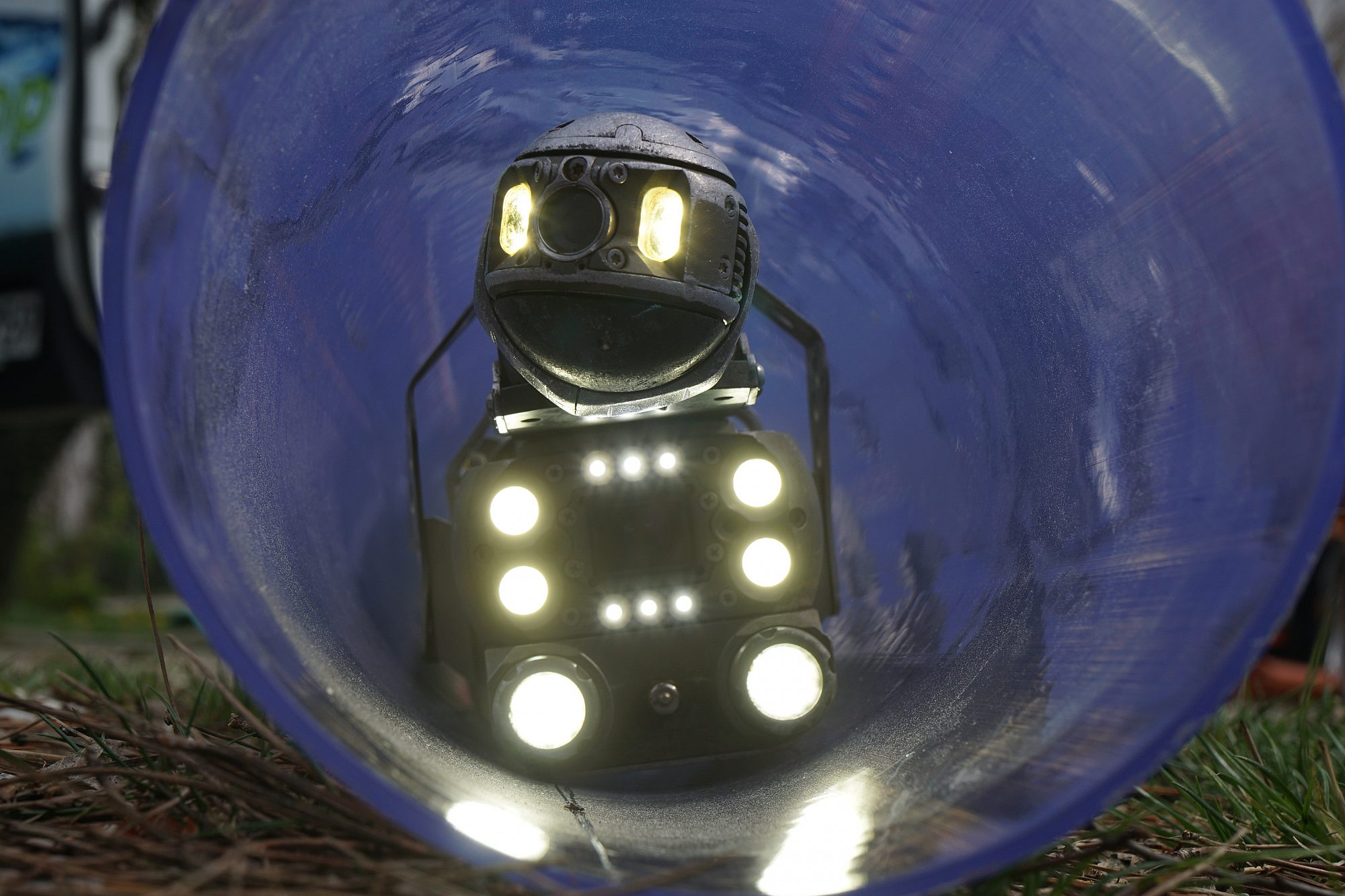 Der Einblick in ein Rohr zeigt einen Kanalroboter mit vielen Lampen, der gerade auf den Betrachter zufährt.