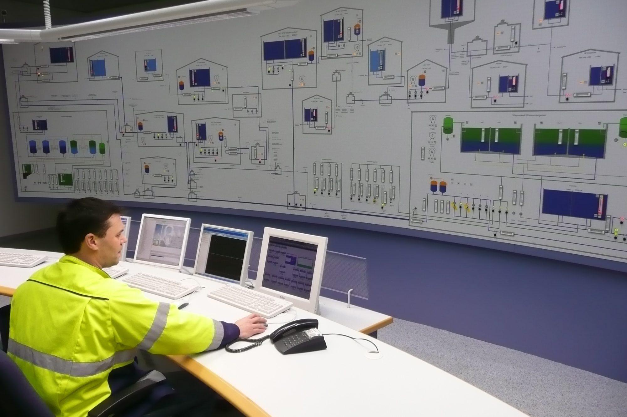 Ein Techniker sitzt an einem Tisch mit Computermonitoren vor einer großen Wand mit technischen Diagrammen und Anzeigen zur Überwachung von Anlagenteilen.