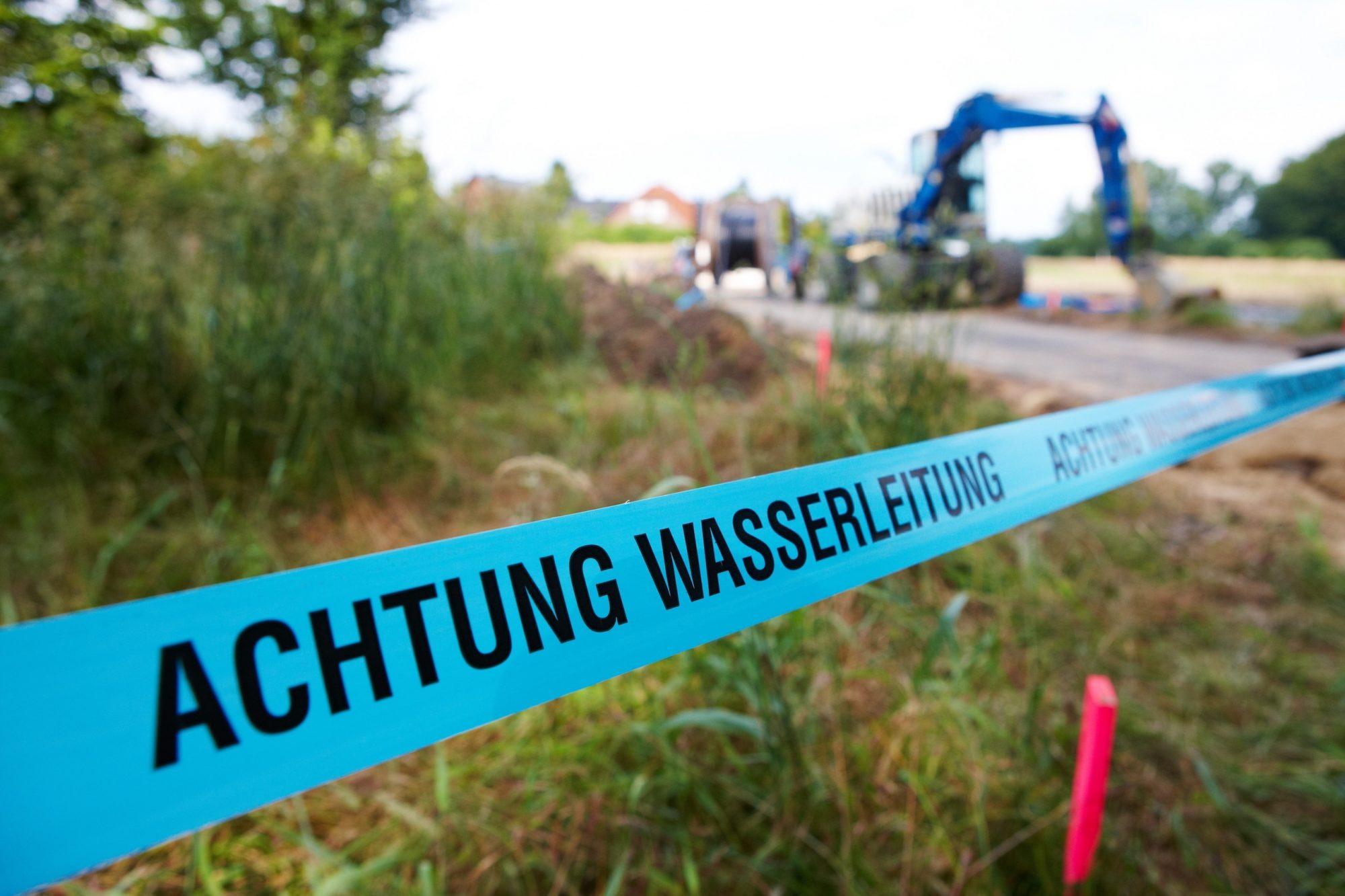 """Symbolfoto """"Achtung Wasserleitung"""" (Absperrband)"""