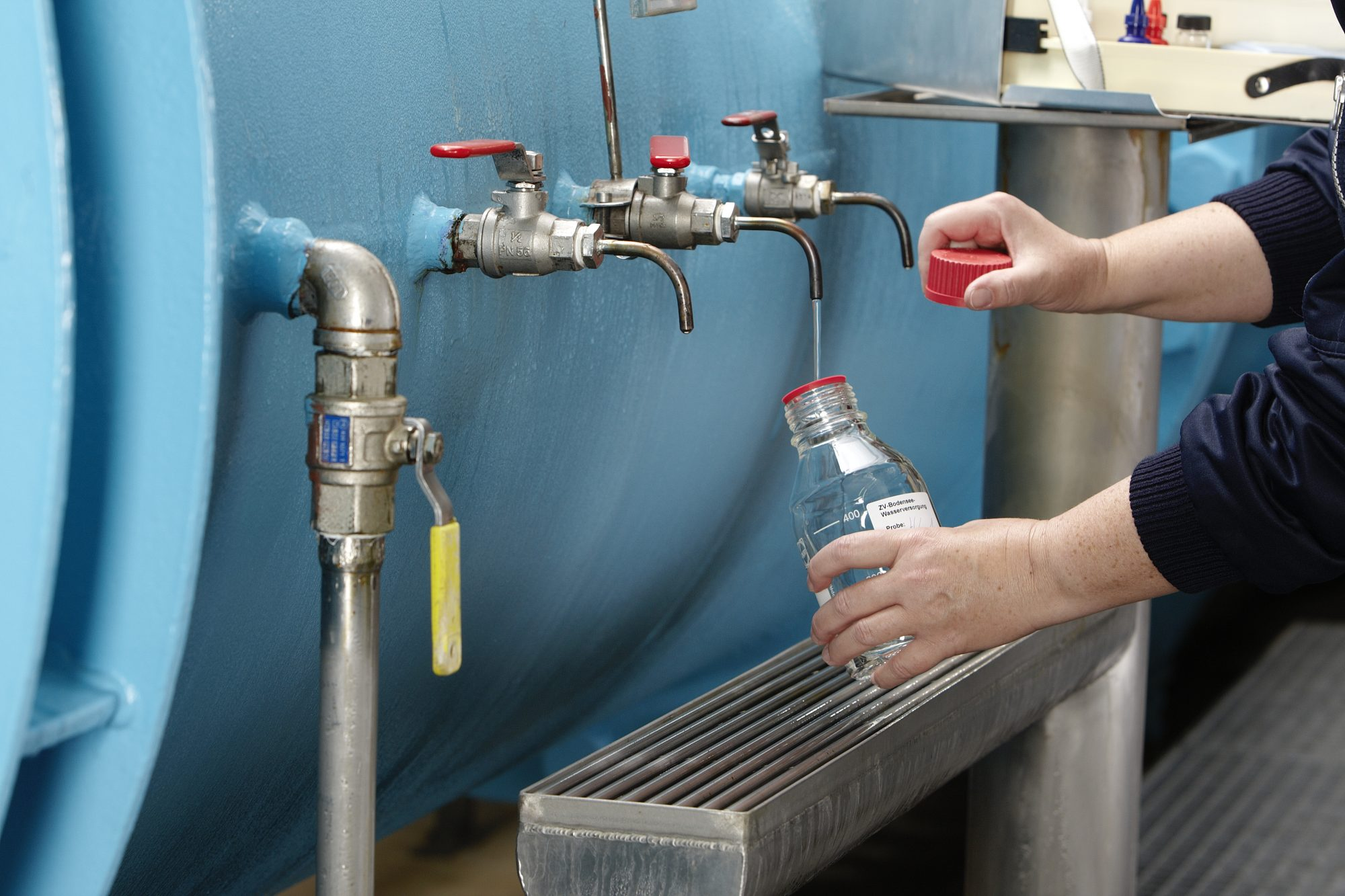 Das Bild zeit Hände im Bildrand, die aus einem Wassertank mit mehreren Hähnen eine Probe entnehmen.
