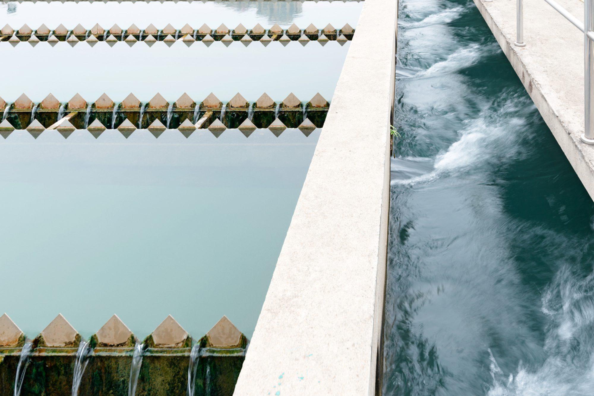 Das Foto zeigt einen Bildausschnitt eines offenen Freibeckens in einer Kläranlage.
