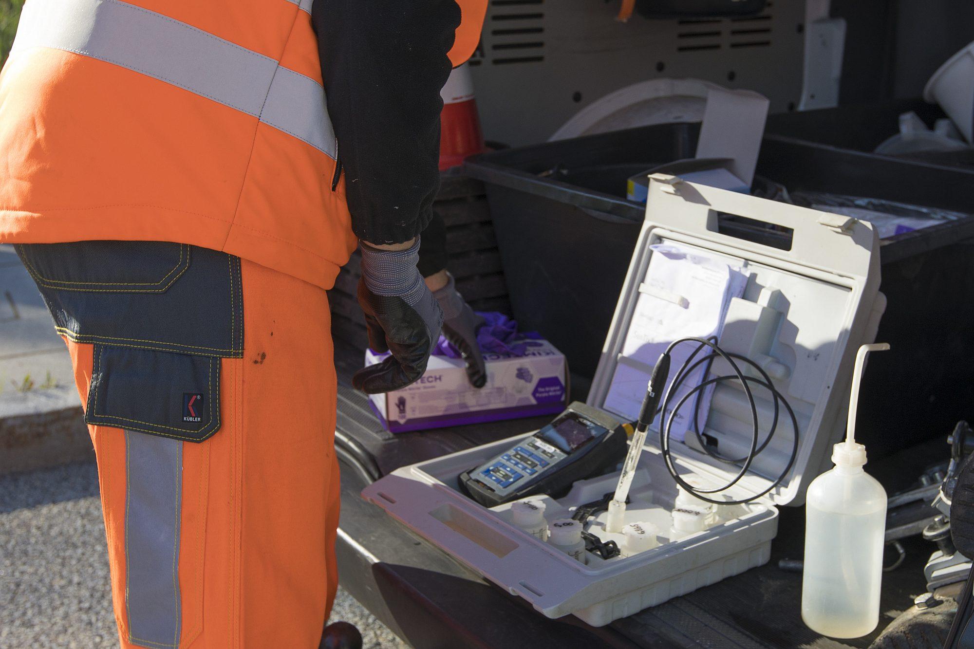 Ein Mann in Arbeitskleidung greift in den geöffneten Werkzeugkoffer mit Analysegeräten für Wasserproben im Kofferaum seines Fahrzeugs.