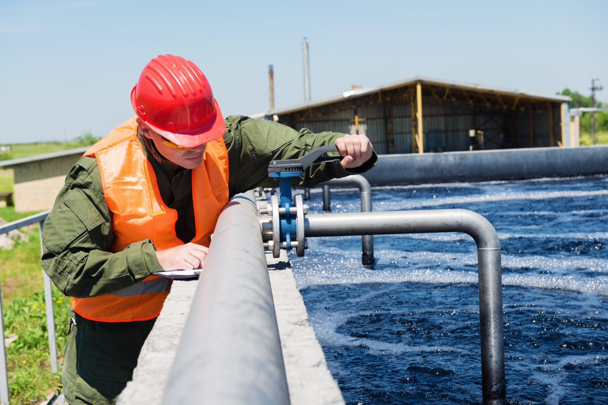 Ein Mann in Arbeitskleidung arbeitet mit Spezialwerkzeug an Ventilen am Rand eines offenen Klärbeckens mit sauberem Wasser..